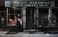 """In the early morning hours of Saturday, Jan. 21, 2012, Rob Schwind shovels the sidewalk in front of the Chagrin Hardware in Chagrin Falls, Ohio. The Shutts family, which has owned the hardware for the last 72 years, was preparing for a community-driven """"Cash Mob"""" of the store to happen that day. (AP Photo/Amy Sancetta)"""