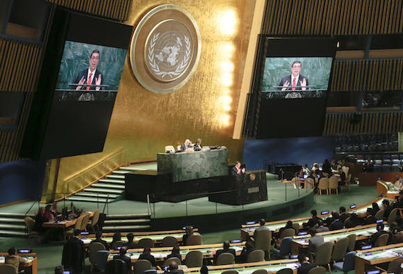 Large video monitors broadcast Cuba's Foreign Minister Bruno Rodríguez as he address a meeting of the U.N. General Assembly, Wednesday Oct. 26, 2016 at U.N. headquarters. The United States has abstained for the first time in 25 years on a U.N. resolution condemning America's economic embargo against Cuba, a measure it had always vehemently opposed. (AP Photo/Bebeto Matthews)