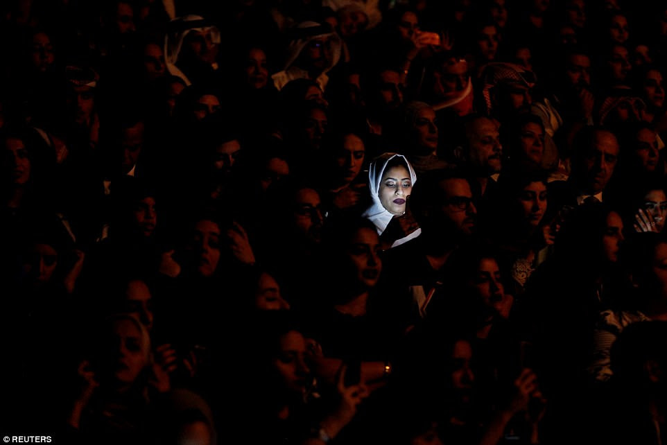 Light from a mobile phone illuminates a Saudi woman's face during Iraqi singer Majid Al Muhandis' live performance as part of Spring of Culture 2017 in Manama, Bahrain, on March 10. Exhibitions, poetry, lectures, film and music celebrate the dawn of spring at the festival, which is now in its 12th year