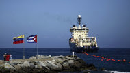 FILE - In this Jan. 22, 2011 file photo, people stand on a breakwater, with a Venezuelan flag, left, and a Cuban flag, as a specialized ship rolls out a fiber-optic cable, suspended from buoys, off La Guaira, Venezuelan coast. Cuban officials last year welcomed the arrival of the undersea fiber-optic cable linking the country to Venezuela, which was supposed to boost web capacity 3,000-fold. Even a retired Fidel Castro had hailed the dawn of a new cyber-age on the island. More than a year later, the government barely speaks of the cable anymore and Cuba's internet connection is still the slowest in the hemisphere. (AP Photo/Ariana Cubillos, File)