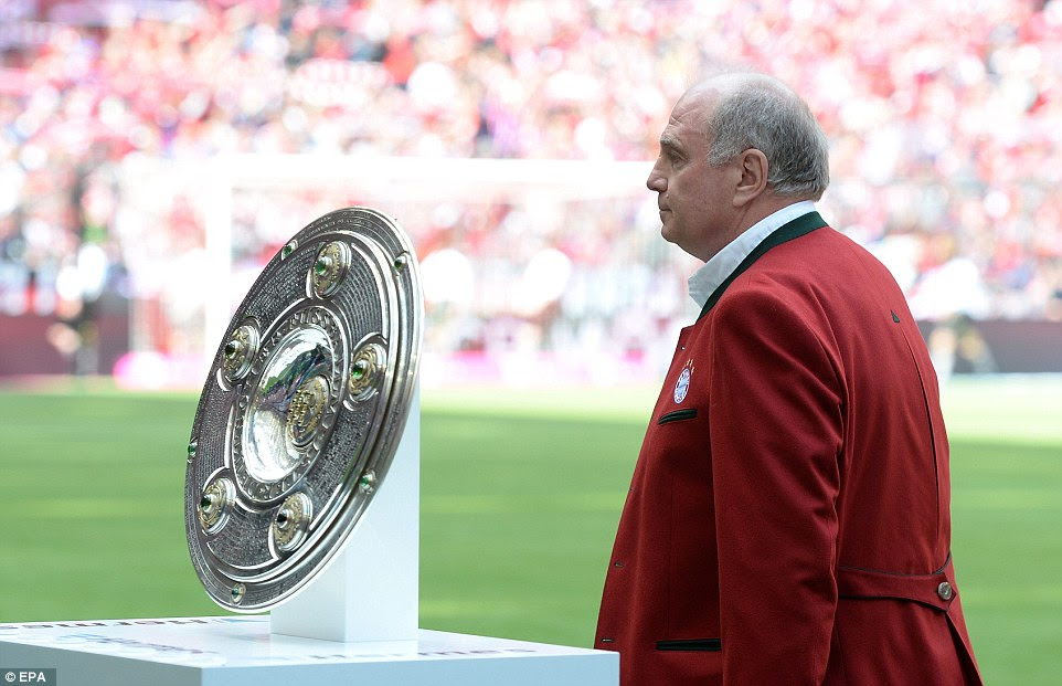 Bayern Munich's former President Uli Hoeness walks past the champion bowl which will be lifted by Munich after the game