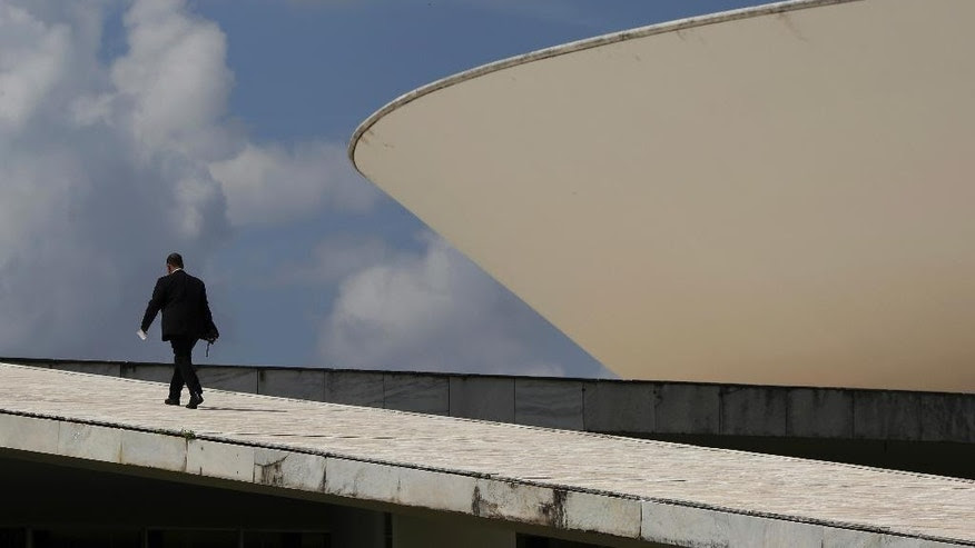 A security guard walks up a ramp leading to the Brazilian National Congress, in Brasilia, Brazil, Thursday, April 13, 2017. Though the deals were often sealed over dinners and coffees, there was nothing casual about the massive corruption scheme that Brazilian prosecutors are investigating involving bribes and kickbacks paid to hundreds of politicians. (AP Photo/Eraldo Peres)