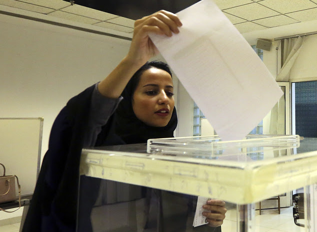 A Saudi woman casts her ballot at a polling center during municipal elections in Riyadh, Saudi Arabia, Saturday, Dec. 12, 2015. Saudi women are heading to po...