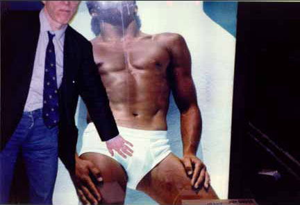 Andy Warhol with hand on crotch of model on Calvin Klein poster