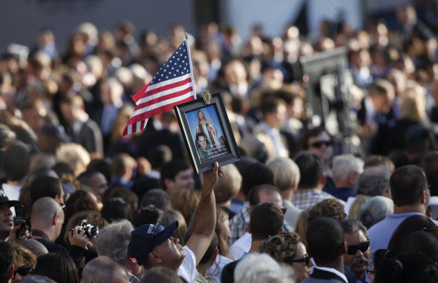 Friends and relatives of the victims of 9/11 gather for a ceremony marking the 10th anniversary of the attacks at the National September 11 Memorial at the World Trade Center site, Sunday, Sept. 11, 2011, in New York. (AP Photo/Jason DeCrow)