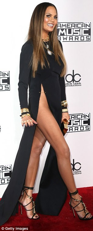 Over exposed: Chrissy Teigen suffered a wardrobe malfunction in a revealing black dress at the American Music Awards on Sunday
