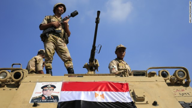 Egyptian soldiers stand guard atop an armored vehicle on a bridge leading to Cairo's Tahrir Square on Friday, July 26.