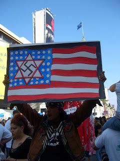 Photo: placard with flag of the USA, with a Star of David on the stars, and a swastika on the Star of David