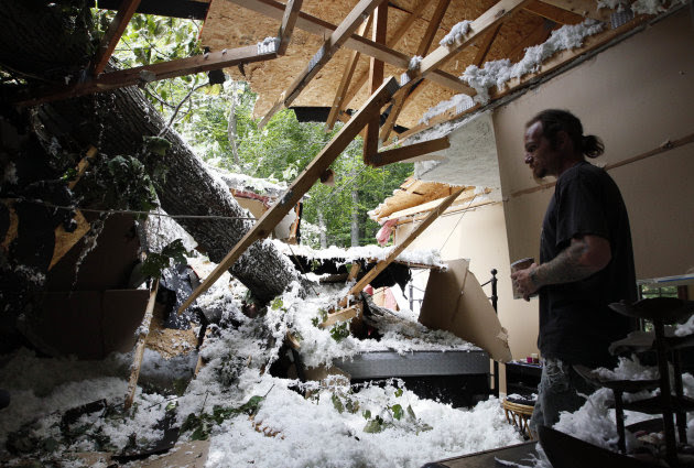 Chester Vickers surveys the bedroom of his girlfriend's daughter, which was heavily damaged by a tree that fell in high winds caused by Hurricane Irene in Port Deposit, Md., Monday, Aug. 29, 2011. (AP