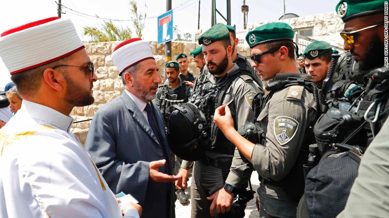 Palestinian Muslim clerics speak with Israeli border guard outside the Lions Gate in Jerusalem's Old City on July 21, 2017.