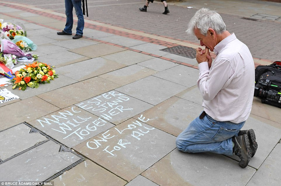 Offering prayers: A man kneels down and prays close to floral tributes left in St Anne's Square Manchester this morning