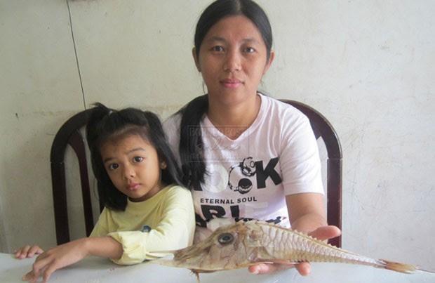 Siti Kadariah segura o peixe fisgado por seu marido (Foto: Reprodução/Facebook/BorneoPost)