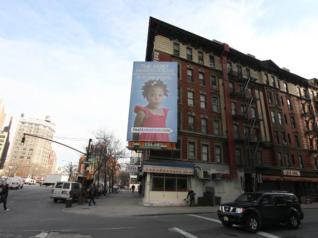Cartaz de grupo antiaborto no SoHo, em Nova York, diz: 'o lugar mais perigoso para um afro-americano é o ventre'. O anúncio, do grupo antiaborto 'Life Always', provocou indignação em grupos pró-minorias, que o consideraram preconceituoso. A entidade afirmou que teve o objetivo de provocar um debate sobre a questão do aborto entre as minorias americanas. O anúncio deve ficar ali durante três semanas. (Foto: James Ambler/Barcroft USA/Getty Images)
