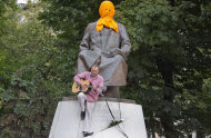 A man plays a guitar while resting on the base of a monument to Kazakh poet Abai Kunanbaev in Moscow on Friday, Aug. 17, 2012, with the face covered with a mask to resemble feminist punk group Pussy Riot members. The three women in the band Pussy Riot have been in jail for more than five months because of a prank in Moscow's main cathedral against Russia's Vladimir Putin, and they face a maximum seven years in jail, as they await a verdict Friday on charges of hooliganism motivated by religious hatred. (AP Photo/Yevgeny Feldman, Novaya Gazeta)