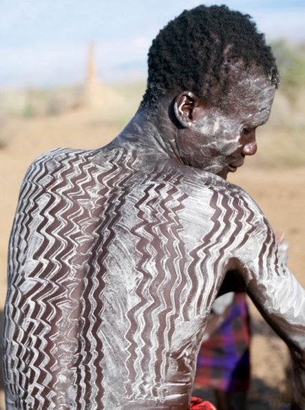 Africa | A Nyagatom man is decorated with white chalk, pulverised rock or other natural pigments before a dance. Omo Valley, southwest Ethiopia | ©Nigel Pavitt
