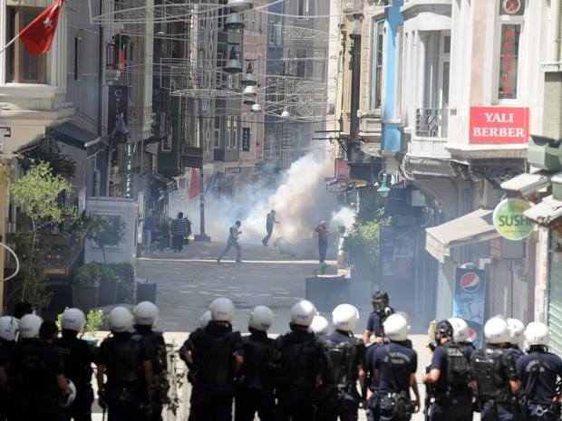 Policiais em formação tentam conter manifestantes durante protesto na Turquia neste sábado (1º). (Foto: Bulent Kilic/AFP)