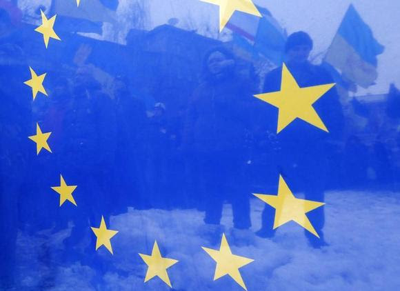 Pro-European integration protesters are seen through an EU flag during a rally near the Interior Ministry headquarters in Kiev December 17, 2013. REUTERS/Alexander Demianchuk