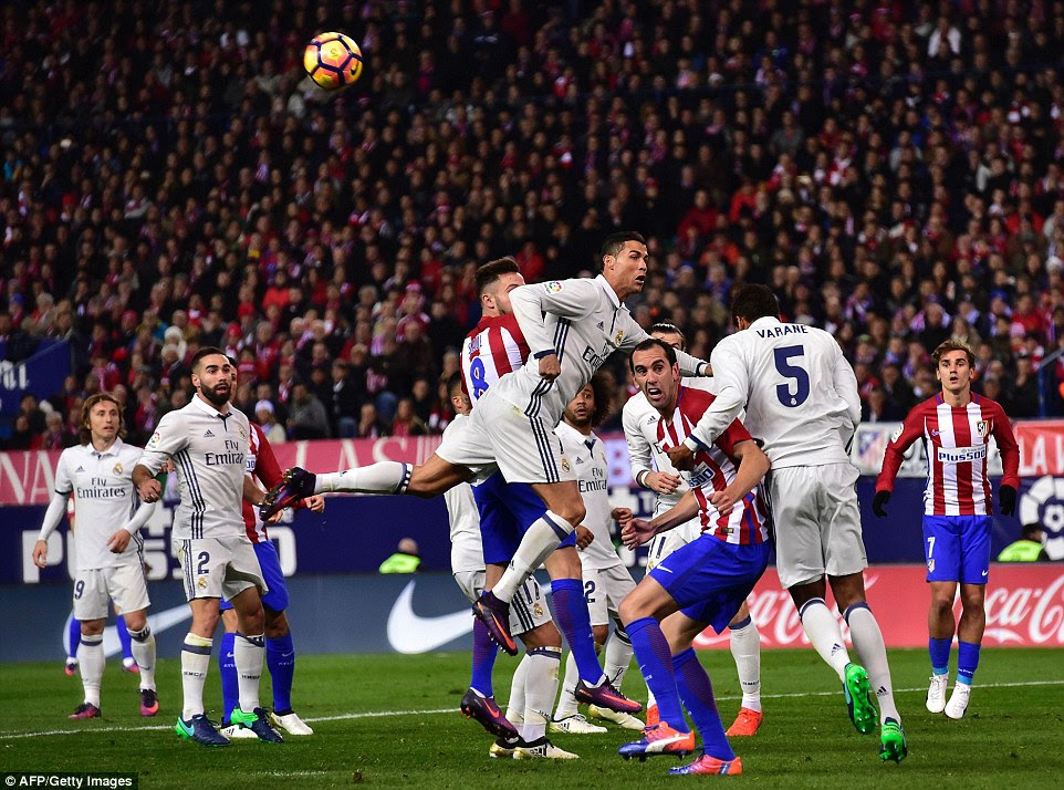 Cristiano Ronaldo rises highest in the penalty area but is unable to connect with the cross as a crowd of players watch on
