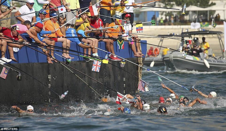 Nadadores chegar para bebidas pendiam para a água por sua equipe como eles competem durante a maratona