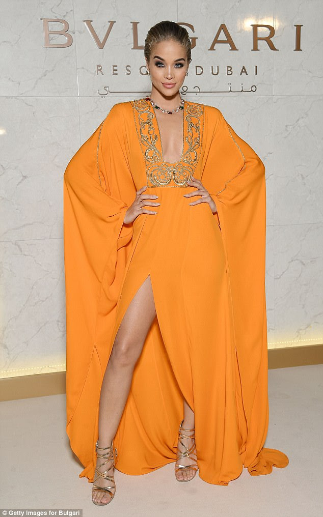 Sweet: Jasmine Sanders rocked a bright orange kaftan with golden embellishments lining her chest and a thigh-high slit in the hem