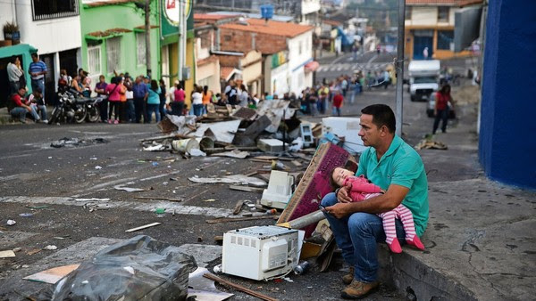 Human cost: A father and daughter rest while someone holds their place in a food queue in San Cristobal, Venezuela, amid shortages of basic goods