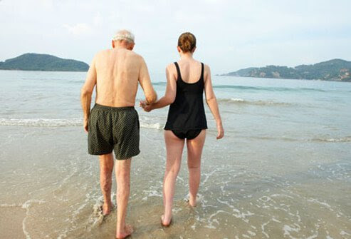 A woman guides a senior man into the ocean.