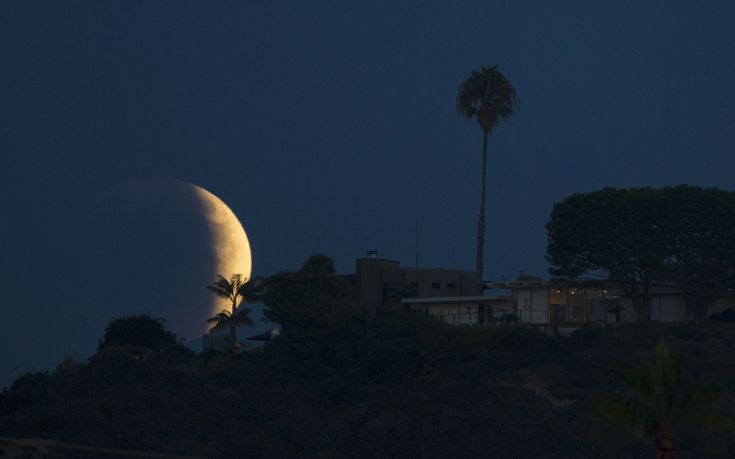 A blood red moon rises behind a hilltop residence in Solana Beach