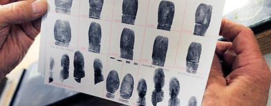 Senior Deputy Jerry Anttila looks at a set of fingerprints for an unidentified suspect during the booking process at the Arapahoe County Justice Center in Centennial, Colo. (AP/Chris Schneider)
