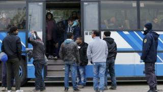 Migrants enter a bus at the Slovenian-Croatian border town of Lendava
