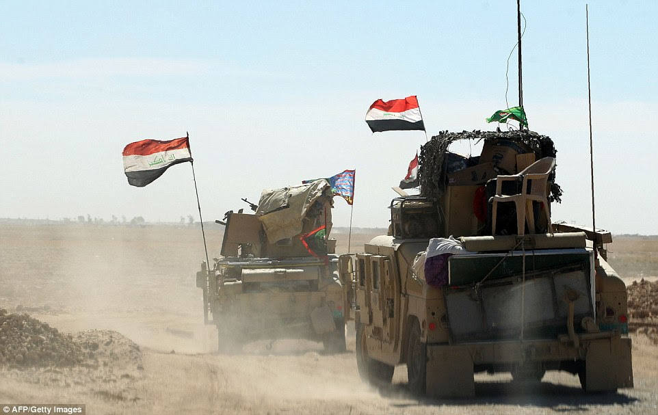 Flags are waved from the military vehicles yesterday on the way to Mosul as the soldiers warn that there could be a bloody final battle