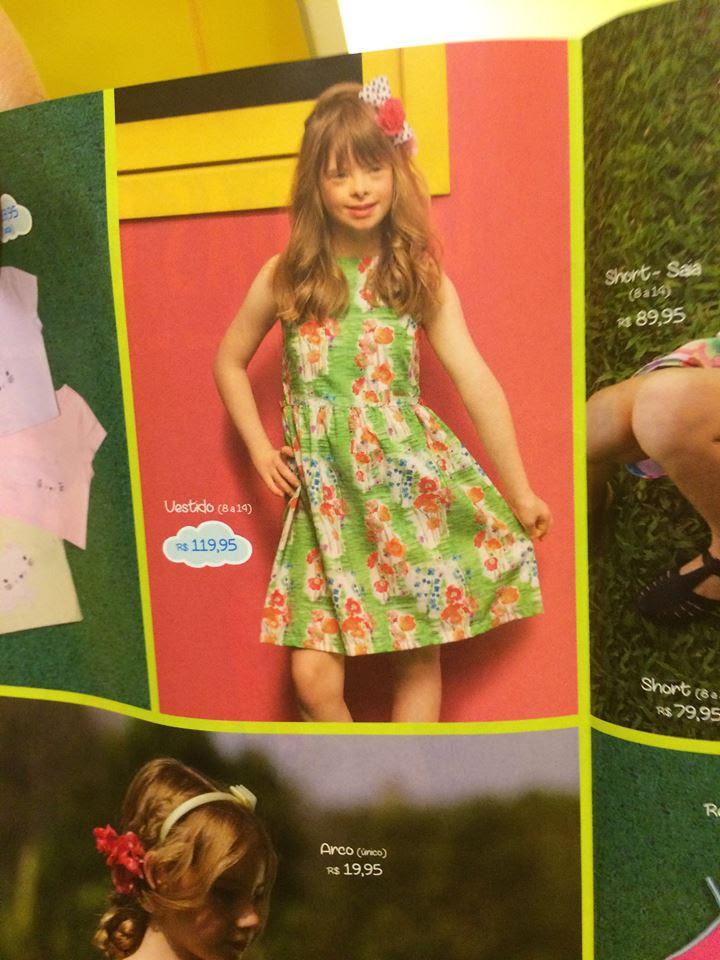 menina com sindrome de down veste vestido verde em catalogo.