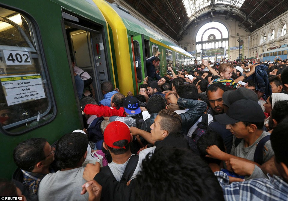 Fighting: As they pushed and shoved to be allowed on to the train, some of the desperate migrants began fighting among themselves