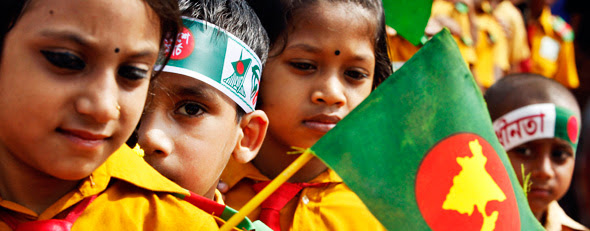 Young Bangladeshi children hold the national flags as they pay tribute to martyrs of the liberation war at the National Memorial during the Independence Day celebrations at Saver on the outskirts of Dhaka, Bangladesh, Monday, March 26, 2012. (AP Photo/Pavel Rahman)