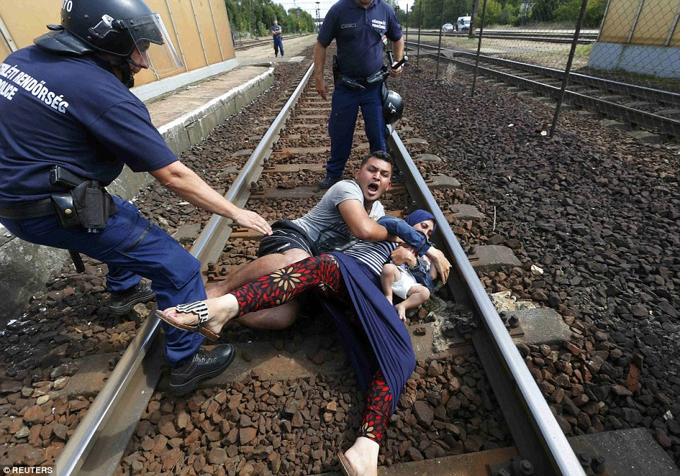Danger: In one particularly harrowing sequence of images a father overcome with emotion tries desperately to protect his wife and child from being taken away - lying down on the tracks in protest