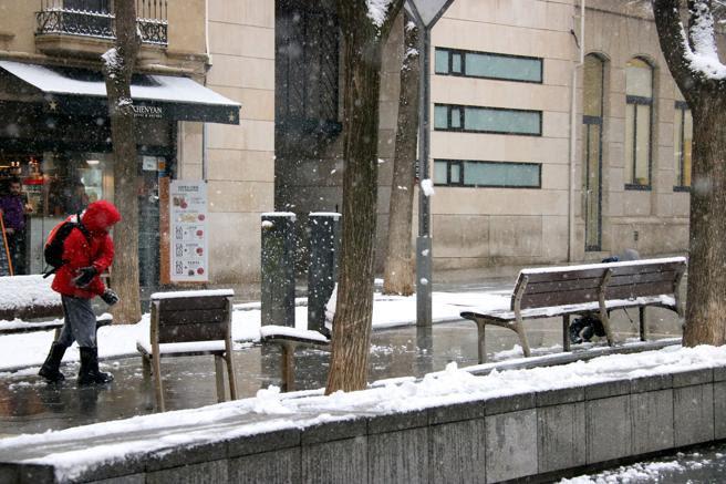 Un niño jugando con la nieve en la plaza de Sant Roc de Sabadell