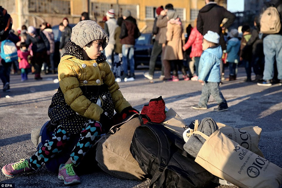 A child sits on bags and waits while refugees form a line behind her to receive food handouts at the port of Piraeus