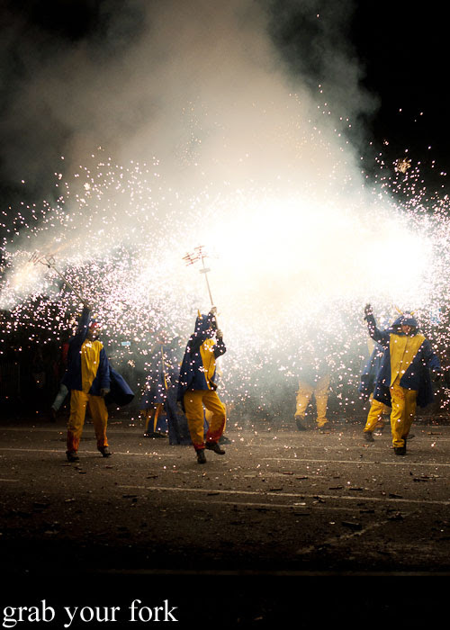 Diables devils in blue and yellow spraying fireworks at Correfoc Fire Run for La Merce 2013