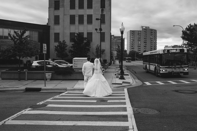 The bride and groom walk across a crosswalk like The Beatles Photograph in downtown Rockford Illinois.