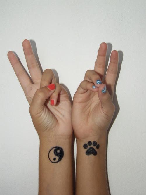 Paw Print And Yin Yang Tattoos On Wrists