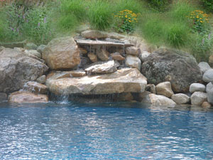 Beautiful Swimming Pool Designs with Travertine Pavers and Waterfall