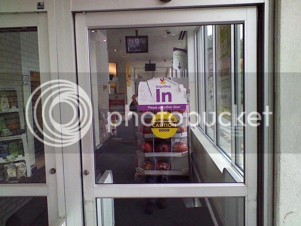Door into store reads 'In/please use other door'