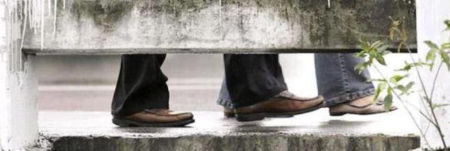 man sleeping under sidewalk - top half only