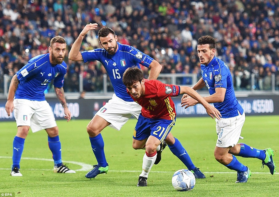 Manchester City playmaker David Silva (centre) uses his magical feet to lose three Italy defenders