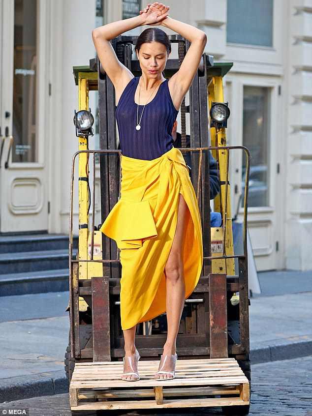 Um pouco de dança: o modelo nascido no Brasil escorregou em uma blusa listrada azul que mal insinuava seu decote, e depois enfiava a blusa na saia de babados dela.