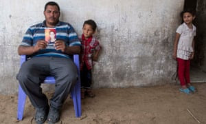 Suleiman Loulahi holds up a picture of his son Bilel, aged 17, a pupil at the Doha school in Rafah who was killed in an Israeli strike on 2 August last year.