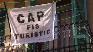 Pancarta contra la proliferació d'apartaments turístics en un balcó de Barcelona