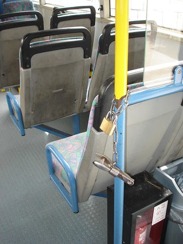 A hole puncher at the rear door of the bus