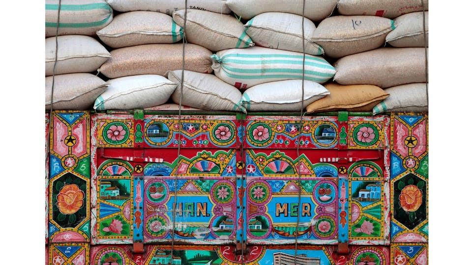 Un camión decorado que lleva sacos de trigo en Charsadda