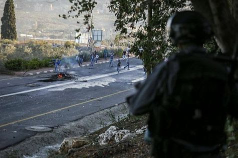 Arab youth throw rocks at Border Police at the entrance to Kfar Kanna in the Galilee, in northern Israel.