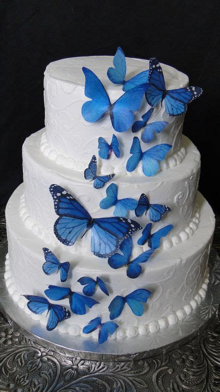 3 tiered white wedding cake with blue wafer butterflies